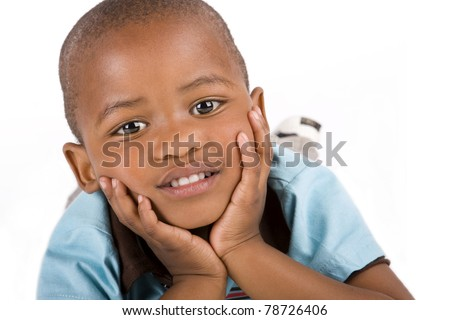 Adorable 3 year old black or African American boy laying with his hands on his chin smiling - stock photo