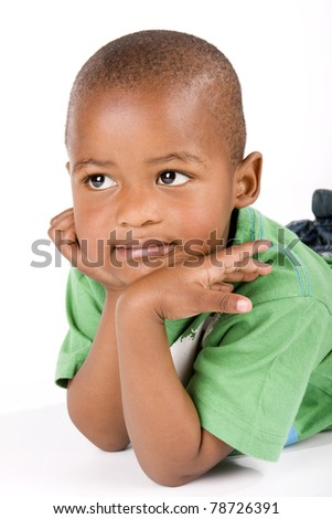 Adorable 3 year old black or African American boy lying on the floor staring into space - stock photo