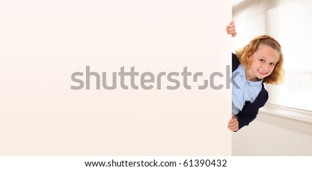 Adorable 7 year old girl in school uniform peeking out behind wall. Space for copy. - stock photo
