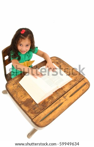 Adorable 3 year old hispanic girl siting in old wooden desk over white background. - stock photo