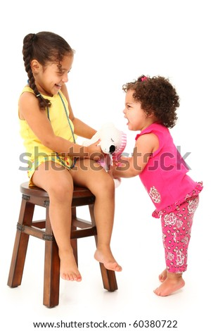 Adorable 3 year old hispanic girl taking baby sister's toy away over white background. - stock photo