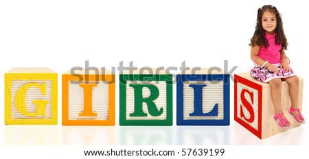 Adorable 3 year old mixed race girl sitting on wooden box over white background. Blocks spell GIRLS. - stock photo