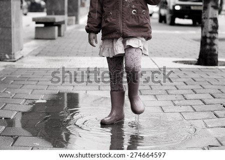 Adorable 4 years old girl at rainy day in springtime - stock photo