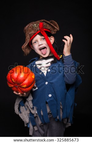 Adorable young boy dressed in a pirate outfit, playing trick or treat for Halloween. Studio portrait over black background - stock photo