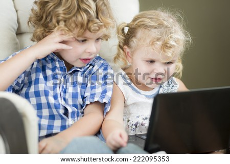 Adorable Young Brother and Sister Using Their Computer Laptop Together. - stock photo