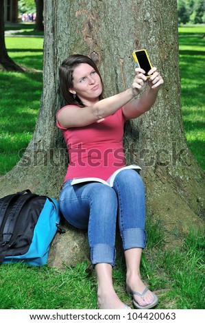 Adorable young Caucasian female student sitting in the shade of a tree taking a picture of herself with a cell phone camera - backpack next to her and book on her lap - making a funny face - stock photo