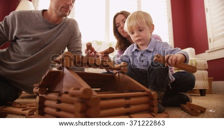 Adorable young children building a wooden house with family. - stock photo
