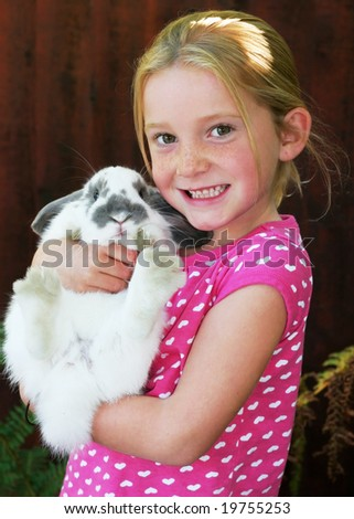adorable young girl holding pet bunny - stock photo