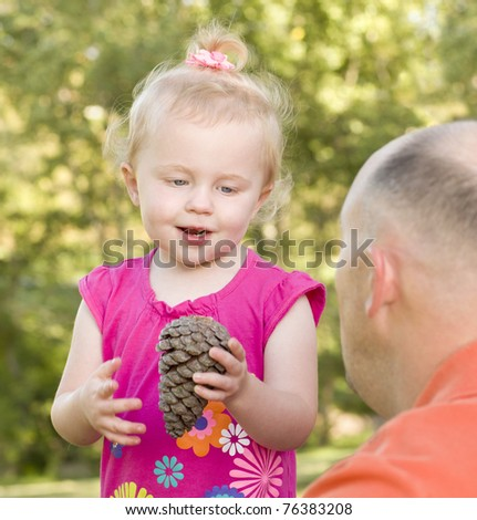 Adorable Young Girl Holding Pinecone Talks to Her Dad in The Park. - stock photo