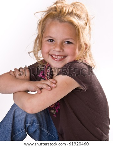 Adorable young girl smiling for the camera in a brown shirt and jeans on a white background - stock photo