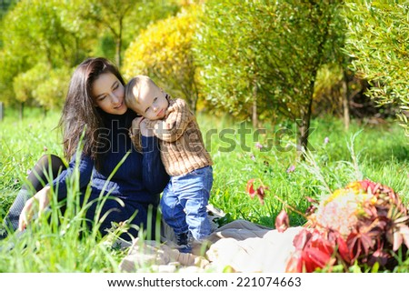 Adorable young mother with toddler son, having picnic on a sunny autumnday - stock photo
