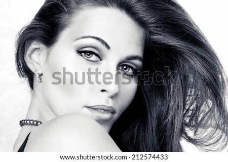 Adorable young woman looking at camera across the shoulder - stock photo