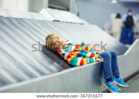 Adoralbe little tired kid boy at the airport, traveling. Upset child waiting with kids suitcase on baggage carousel. Canceled flight due to pilot strike. - stock photo
