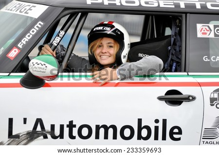 ADRIA, ITALY - MAY 1, 2014: Sensual young pilot girl with blonde hair and helmet smiling inside a sportive racing car after a test drive on Adria at May 1, 2014 - stock photo