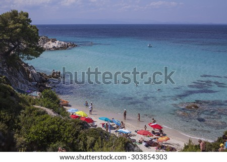 "Adriatic, Greece - June 26 2015: Tourists wild beach ""Oranges"" resort near Vurvuro located on the Halkidiki peninsula.  - stock photo"