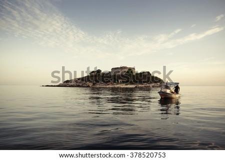 Adriatic Sea. Boat on the background of the island Mamula. Montenegro - stock photo