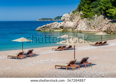 Adriatic sea paradise bay between rocks and mountains. Wooden chaise-longue chairs and umbrellas. Montenegro. - stock photo