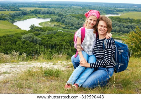 Adult and child standing on a mountaintop near  river.  Mother with little daughter hiking in mountains on vacation - stock photo