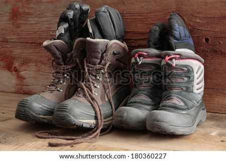 Adult and kids old winter snow boots with gloves inside them standing ready in a rustic wooden cabin to be worn outdoors in the freezing winter weather - stock photo