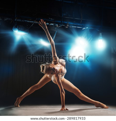 adult ballerina posing on stage in theater against spotlights - stock photo