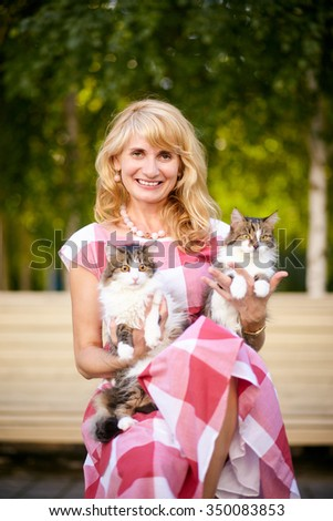 Adult beautiful and smiling woman posing on a chair with cats. - stock photo
