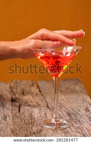 Adult beverage Cosmo colorful drink in martini glass on weathered, rustic tabletop with woman's hand - stock photo