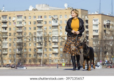 Adult blond woman wolking with big black dog - stock photo