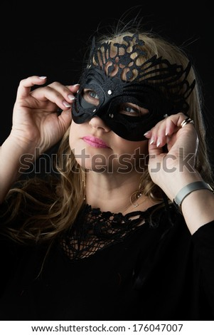 Adult blonde caucasian woman wearing a black lace top a glamor mask and gold earrings. - stock photo