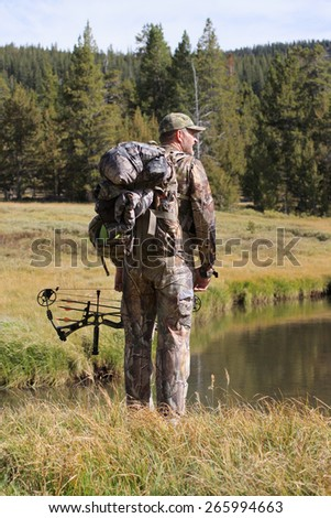 adult bowhunter by stream in remote forest - stock photo
