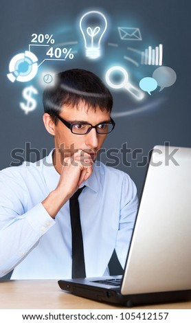 Adult business man working with his computer and different icons of his tasks and functions are flying from screen - stock photo