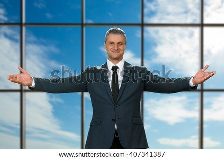Adult businessman's welcoming gesture. Polite executive on sky background. Best chief ever. It's all for you. - stock photo