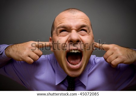 Adult businessman screaming in pain over gray background - stock photo