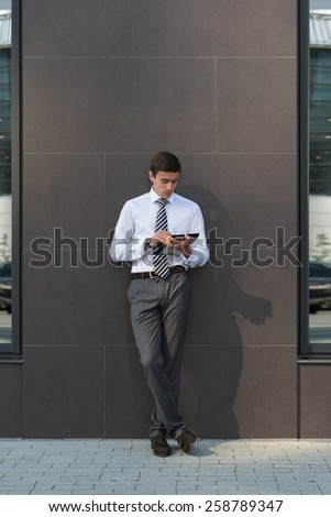 Adult businessman using tablet computer outdoors leaning on wall of office building - stock photo