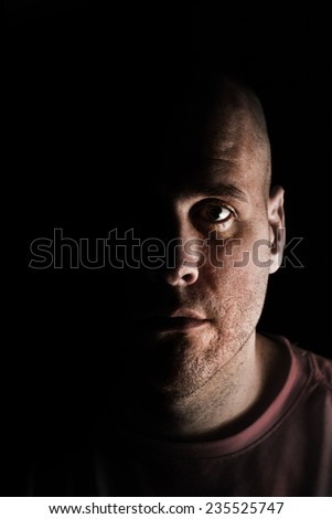 Adult Caucasian white man in deep shadows scruffy and unshaven looking at camera mysteriously while tired exhausted - stock photo