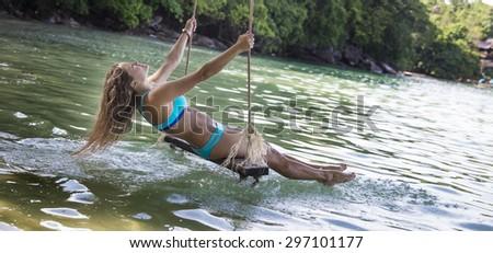 Adult Caucasian woman in blue bikini swinging on a rope swings by the beach. - stock photo