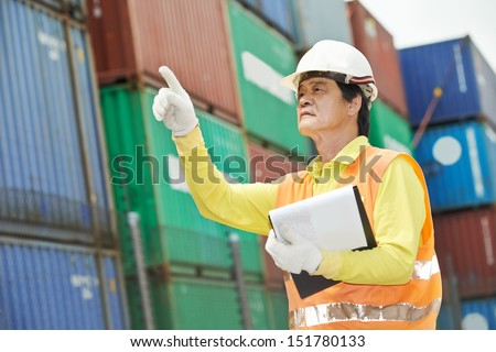 adult chinese terminal cargo dock warehouse worker in front of container - stock photo