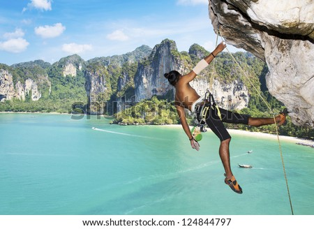 Adult climbing hard overhanging wall in Krabi, Thailand. - stock photo