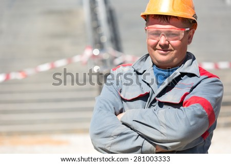 Adult construction male worker in uniform and safety glasses - stock photo