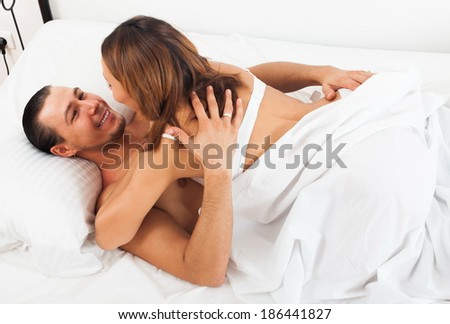 Adult couple having sex on bed in home interior - stock photo