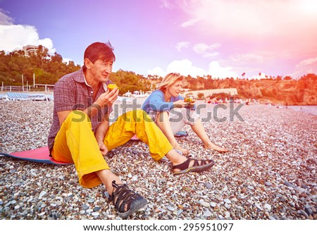 adult couple on the beach eating a ripe persimmon - stock photo