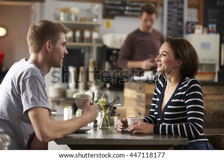 Adult couple talking at a table in a coffee shop, side view - stock photo