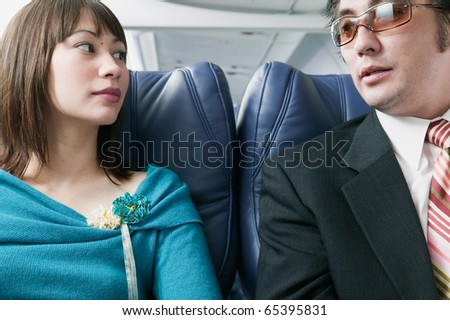 Adult couple traveling in an airplane - stock photo