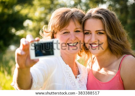 Adult daughter and her senior mother are taking selfie photo with mobile phone - stock photo