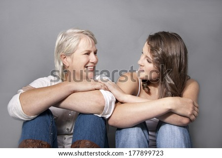 Adult Daughter and mom sitting Laughting close - stock photo