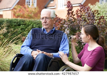 Adult Daughter Comforting Senior Father In Wheelchair - stock photo