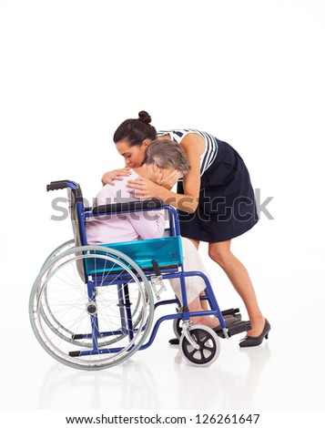 adult daughter hugging and comforting crying disabled senior mother - stock photo