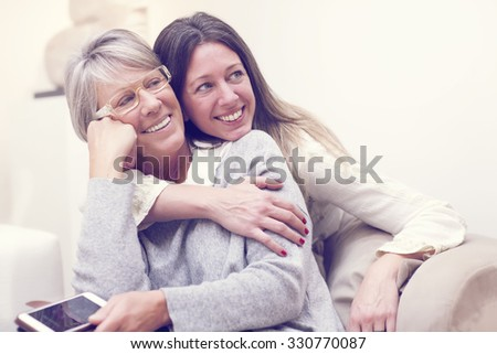 adult daughter hugging her mother - stock photo