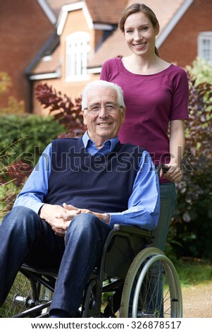 Adult Daughter Pushing Father In Wheelchair - stock photo