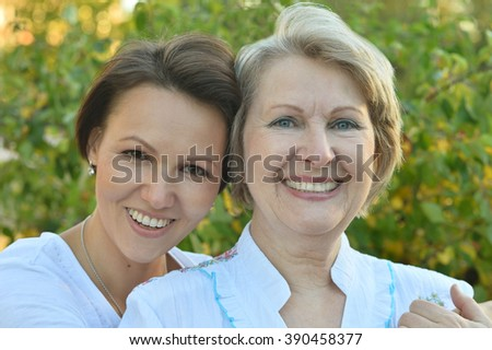 adult daughter walking in autumn park with her mother - stock photo