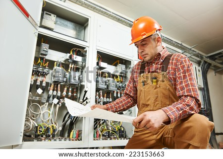 adult electrician builder engineer worker with electric scheme plan in front of fuse switch board - stock photo